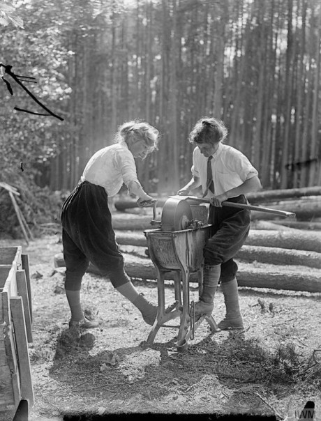 Members of the Women's Forestry Corps grinding an axe. © IWM (Q 30720)