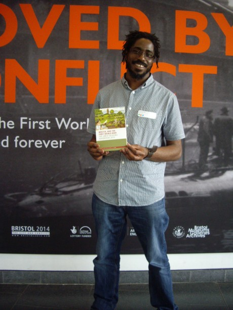 Bristol 2014 commissioned artist Shawn Sobers with the Great Reading Adventure book outside the Moved by Conflict exhibition at M Shed.